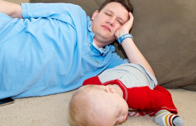 father and son sleeping at first birthday party