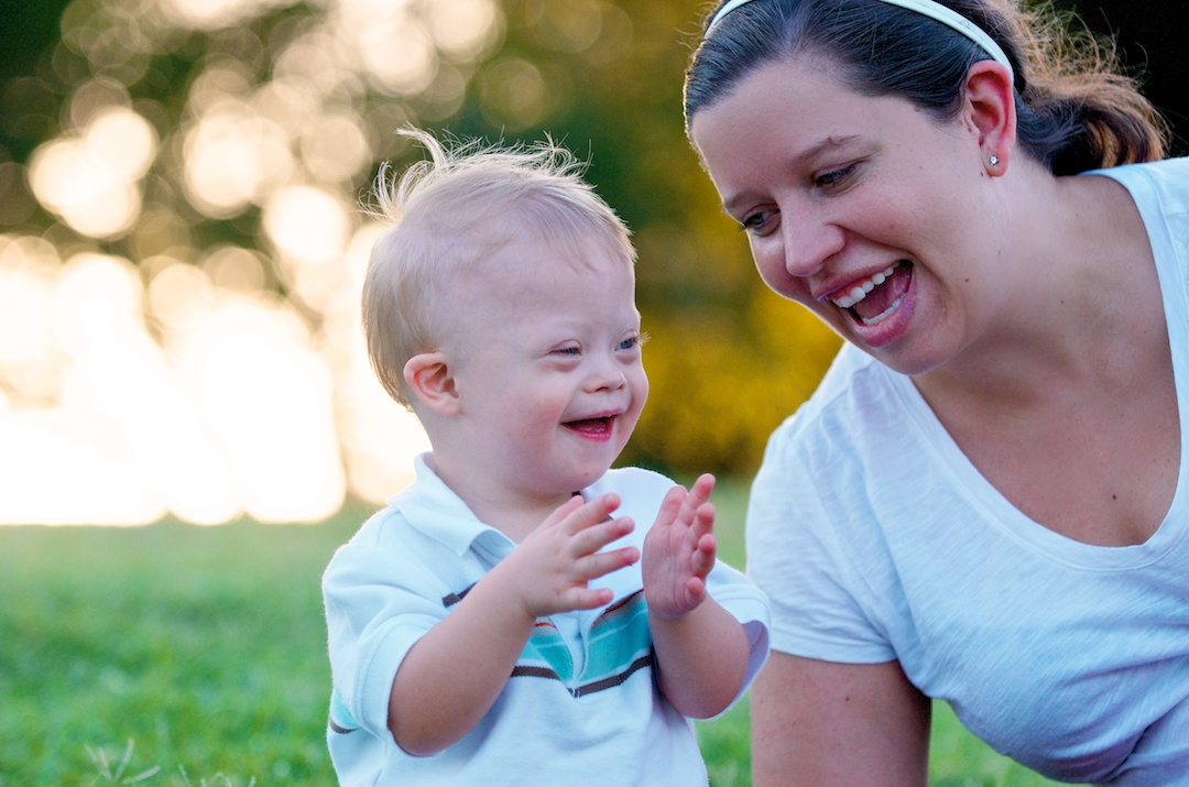 happy baby with down syndrome clapping laughing with mom