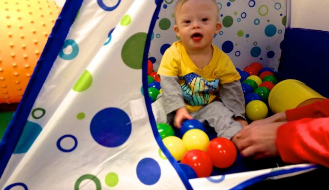baby playing in ball pit special needs