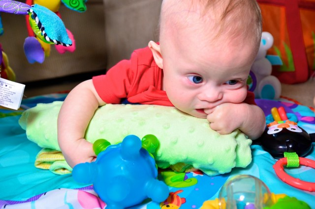 cute baby boy with down syndrome playing