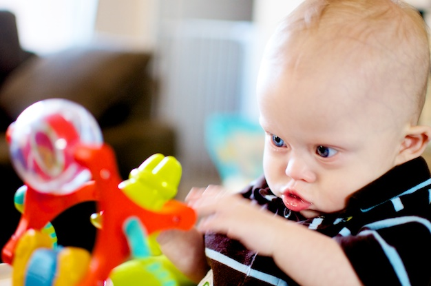 My son born with down syndrome playing with his favorite toys