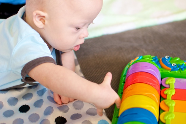 picture of our son with down syndrome playing with fun toys
