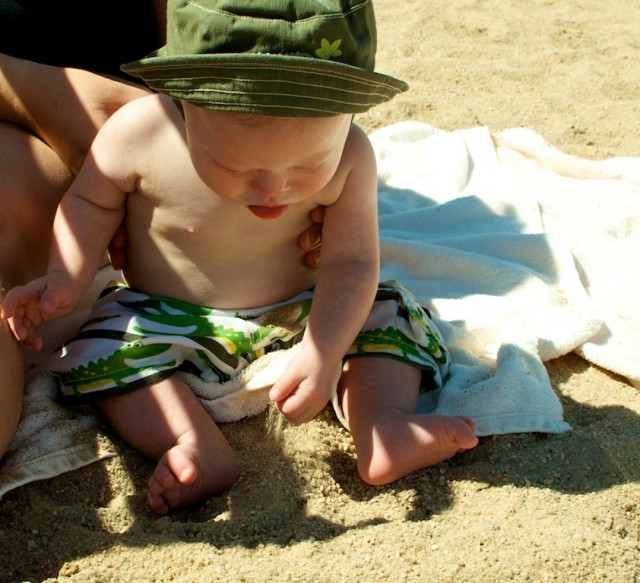 down syndrome baby boy kid playing sand