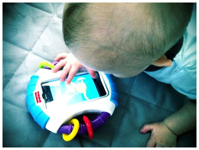 a boy with down syndrome downs playing with the fisher price laugh and learn apptivity case