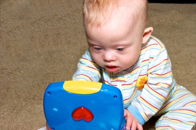 down s syndrome baby boy sitting up toy development