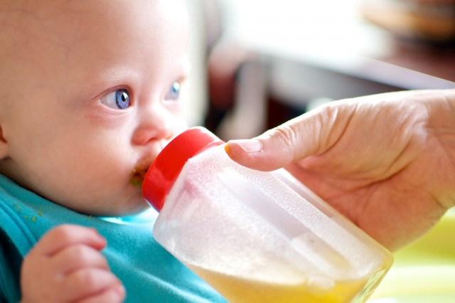 boy with downs down syndrome drinking from sippy cup