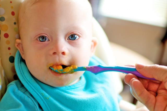 baby down syndrome eating from plastic spoon