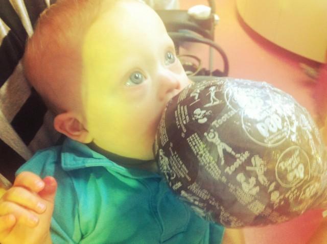 kid boy eating worlds biggest tootsie roll pop sucker