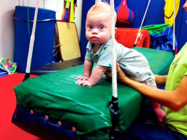 boy with down syndrome on a swing at physical therapy