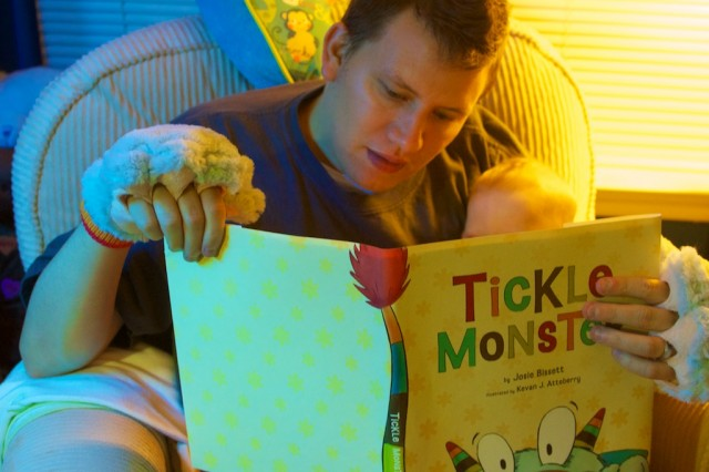Father reading to his newborn born with downs syndrome down