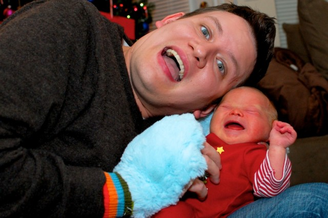 dad tickling his crying son born with Down syndrome