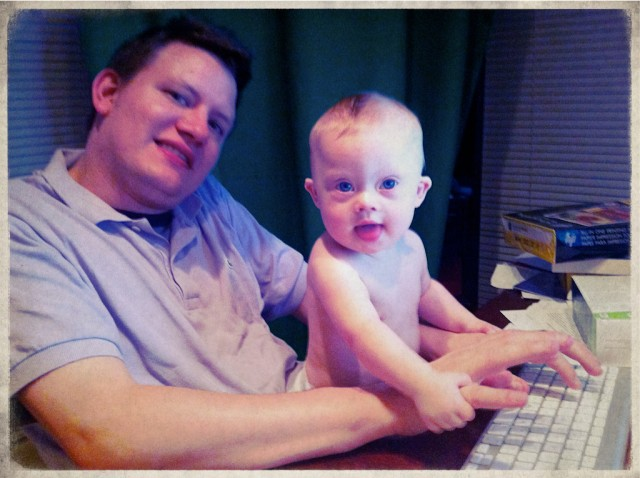 baby born down syndrome playing typing dad father iMac computer