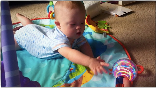 baby down syndrome reaching toy crawling