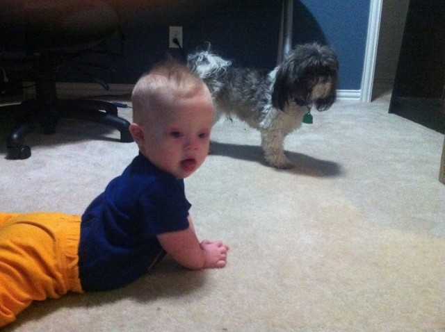 son with down syndrome playing with pet dog