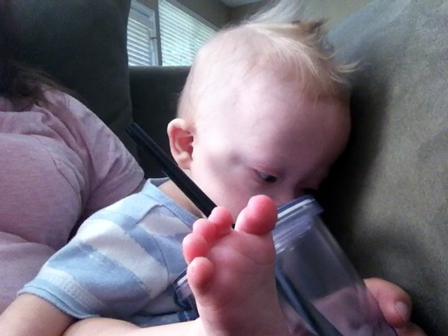 baby down syndrome playing with a cup and straw