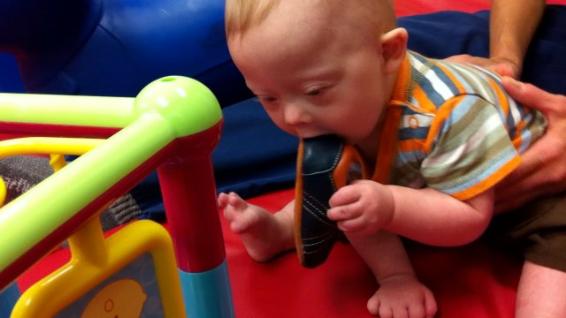 child with down syndrome eating shoe in mouth