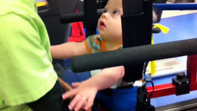 special needs baby in harness during treadmill therapy