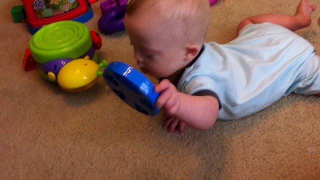 baby with down syndrome playing with toy tambourine