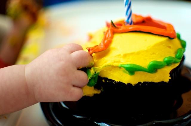 baby grabbing cupcake girl birthday 1 year old