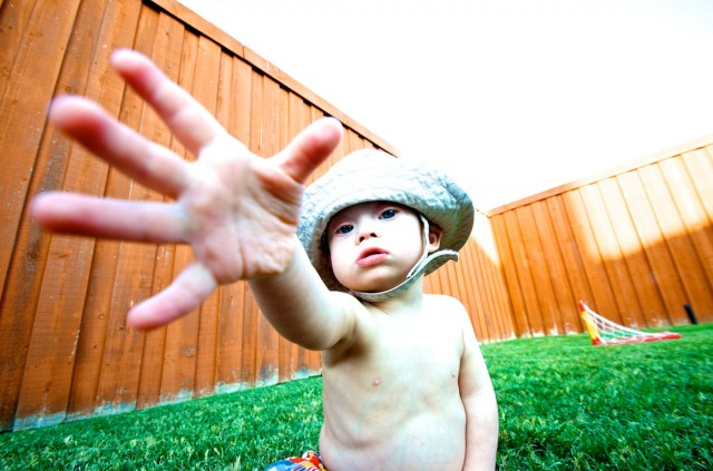 fisherman hat down syndrome child outside playing grass