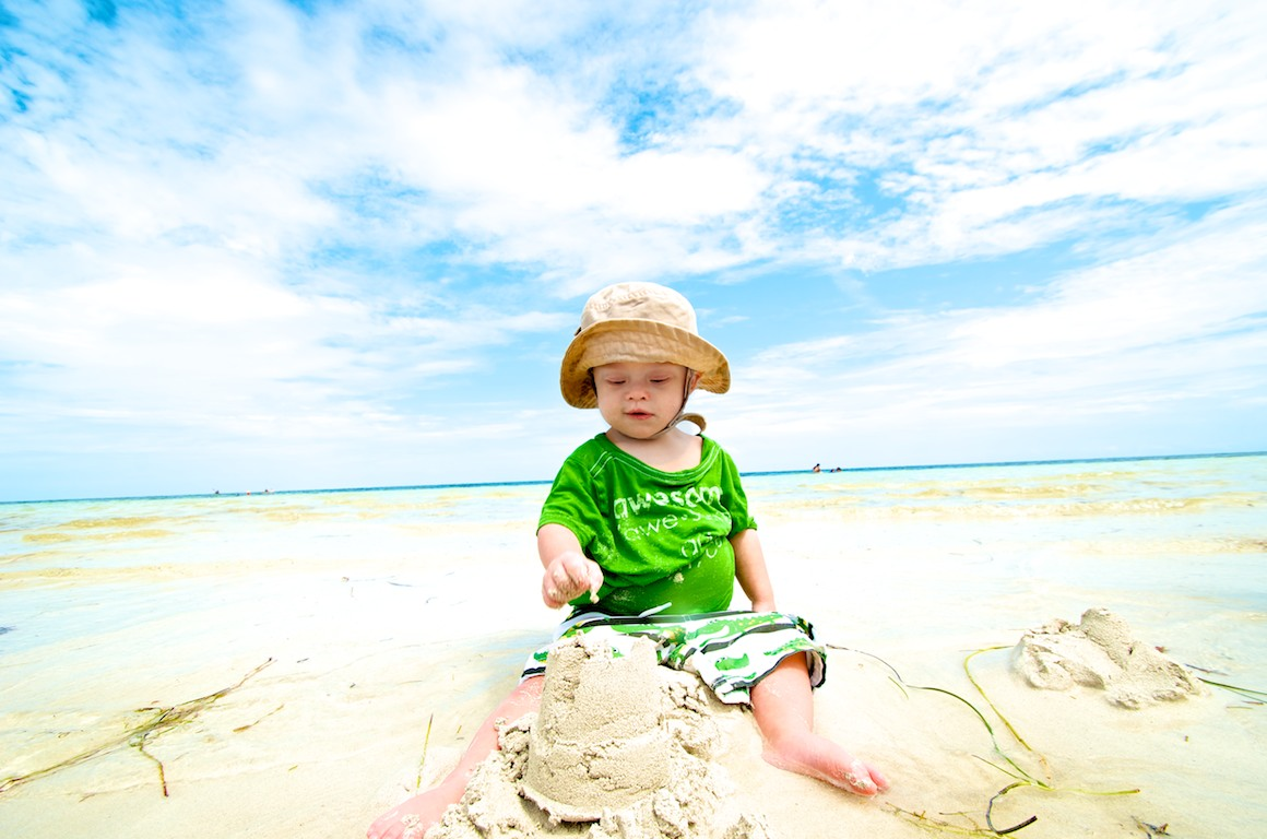 baby with Down syndrome building with sandcaslte on beach