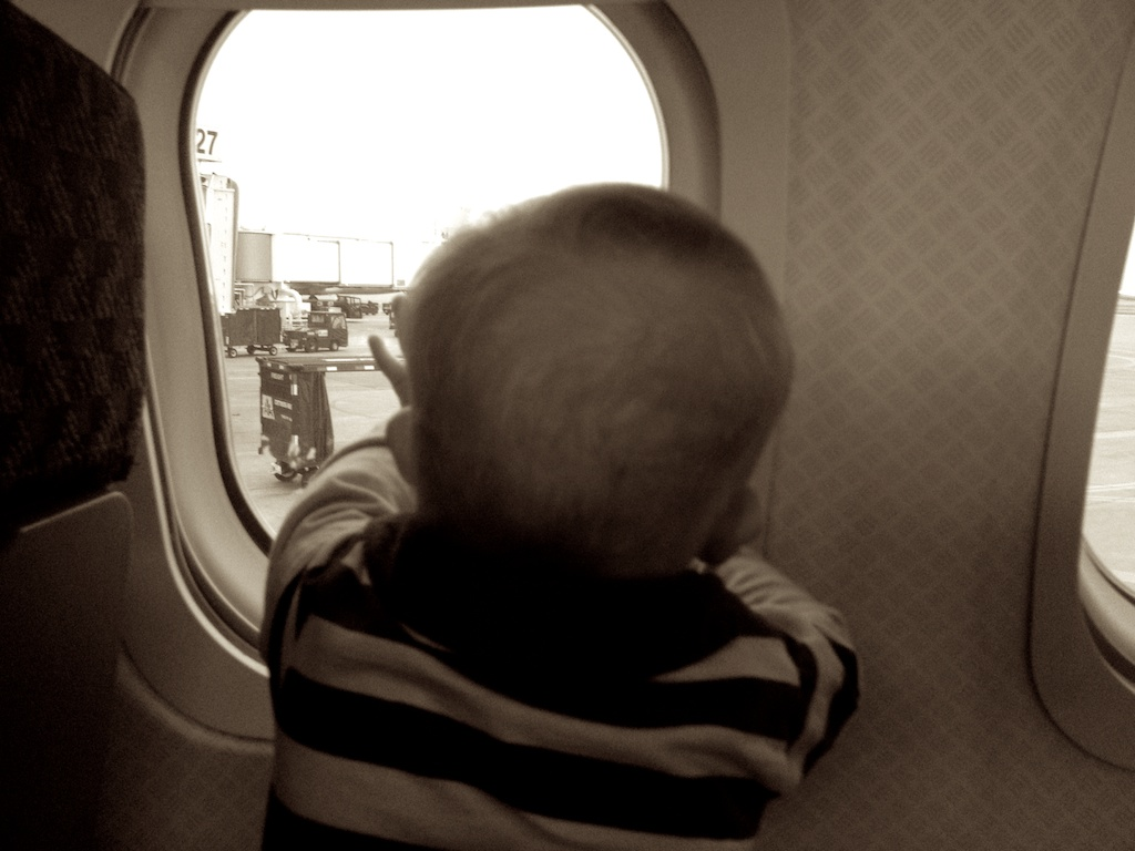 baby boy with down syndrome looking through airplane window