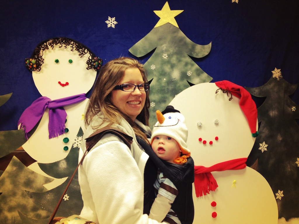 baby wearing snowman hat in carrier mom down syndrome