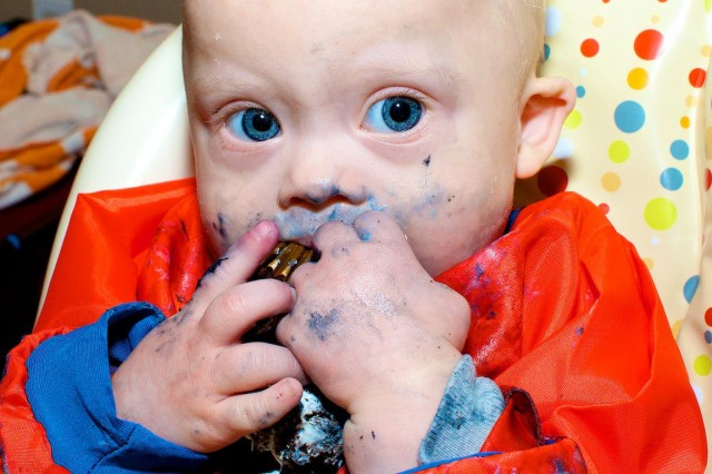 baby with down syndrome eating first birthday cake