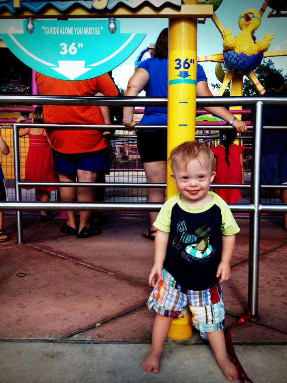 child with down syndrome riding theme park ride