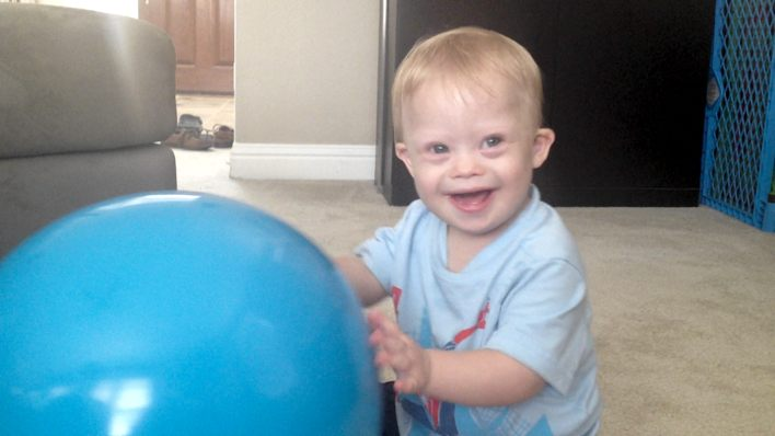 down syndrome baby pushing ball on floor
