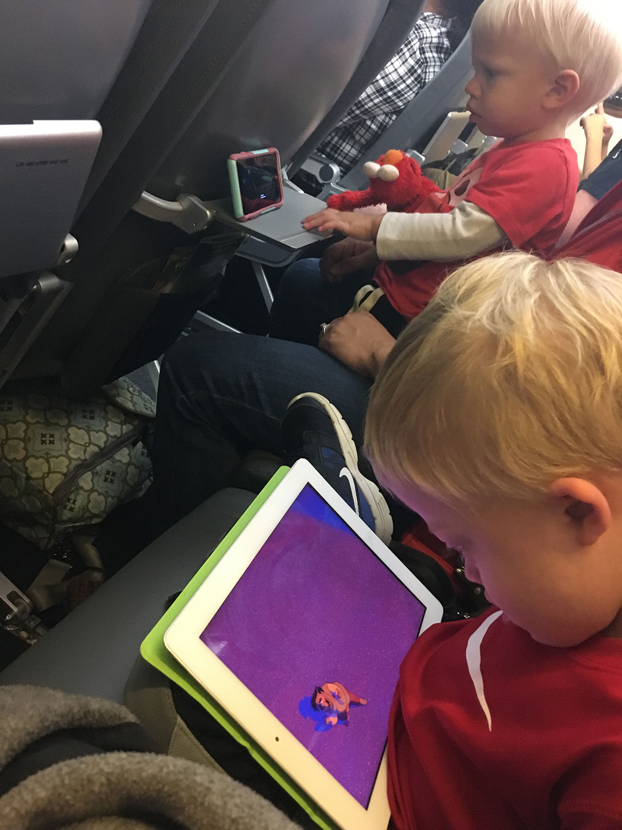 child with down syndrome using iPad on plane