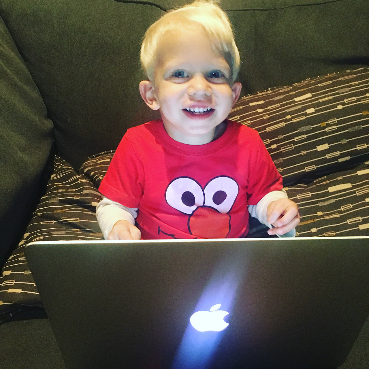 cute baby two year old using macbook pro laptop