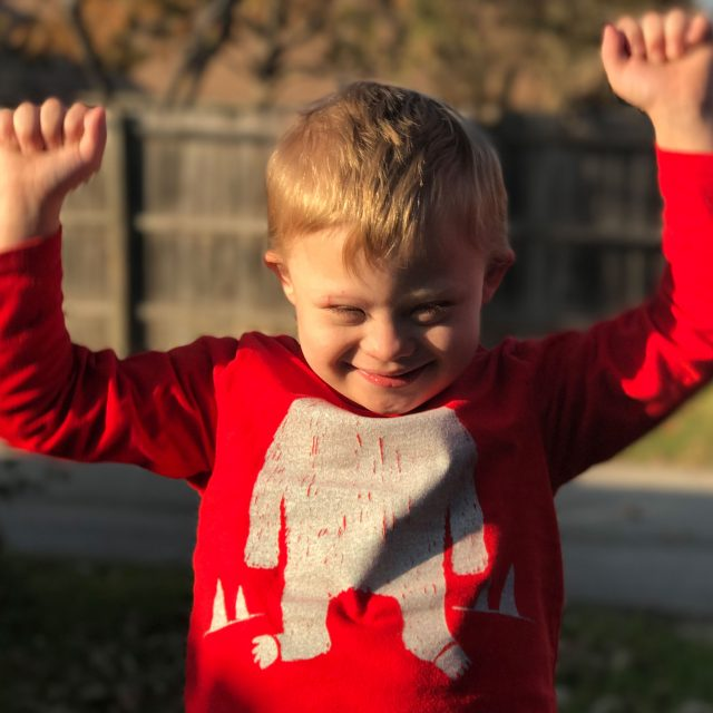 happy boy with down syndrome raising arms up
