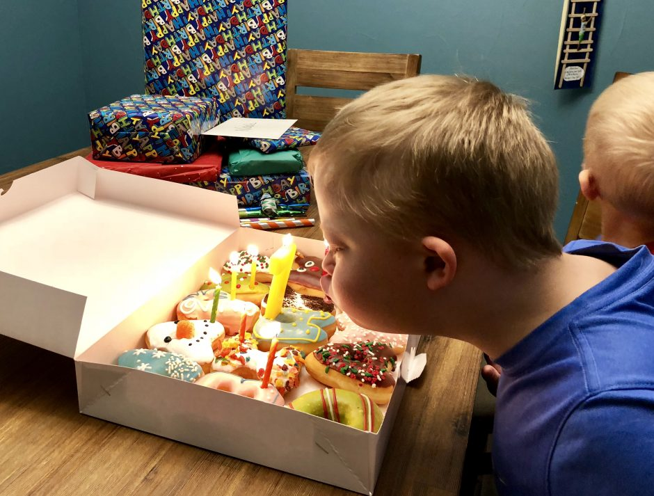 boy with down syndrome blowing out birthday candles