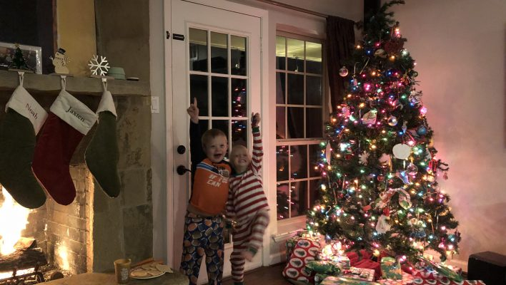 boys giving santa cookies and milk