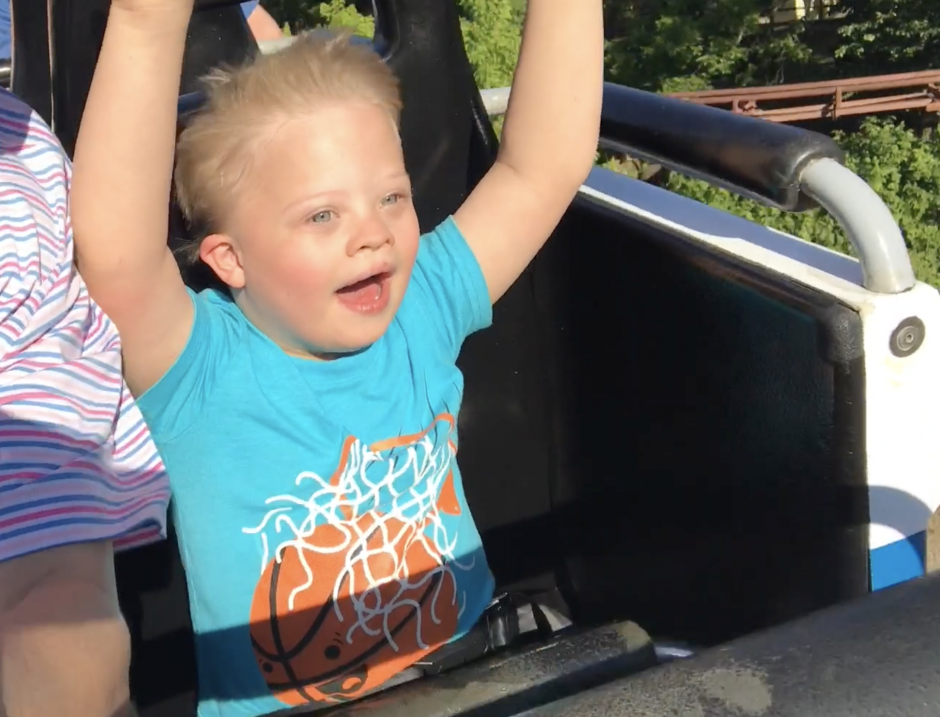 child excited to ride theme park roller coaster