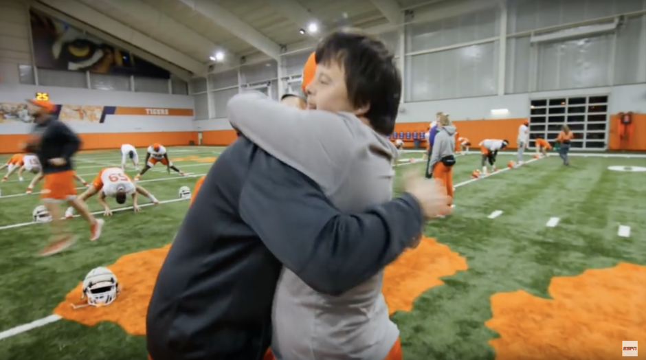 clemson football player hugging equipment manager