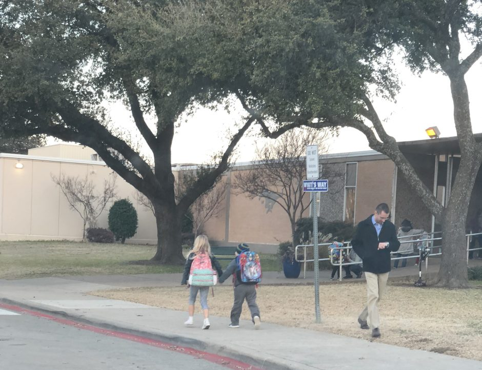girl walking into school with a child with Down syndrome