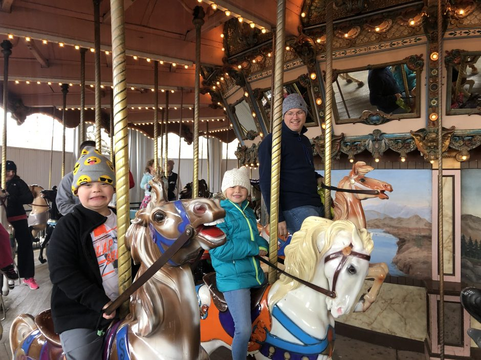 child with down syndrome riding merry go round at six flags