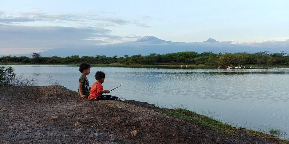 kids sitting by the river in tanzania