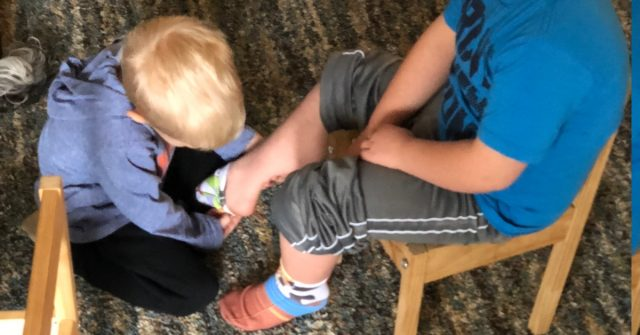 brother helping down syndrome brother putting socks on