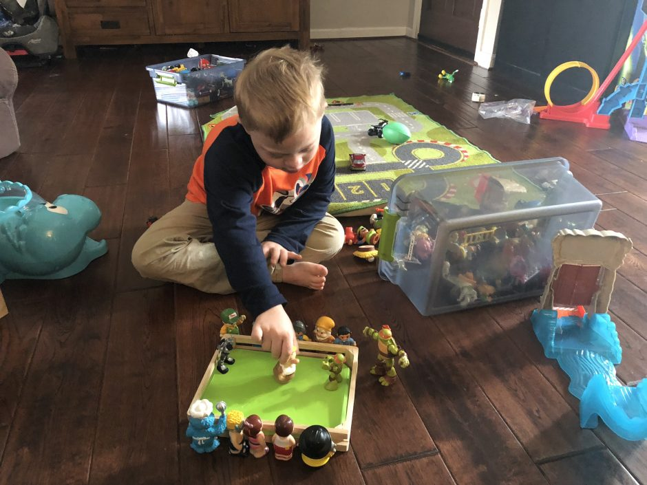 boy with special needs playing with toy figures