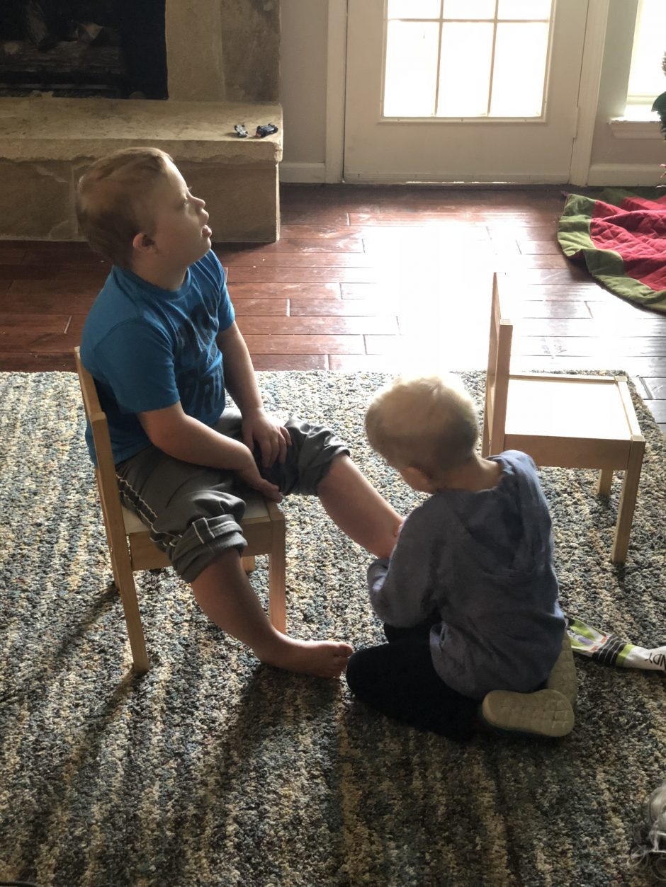 younger brother helping older brother with down syndrome socks